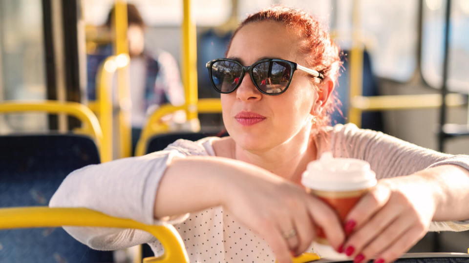 Young woman wearing sunglasses sat on a bus