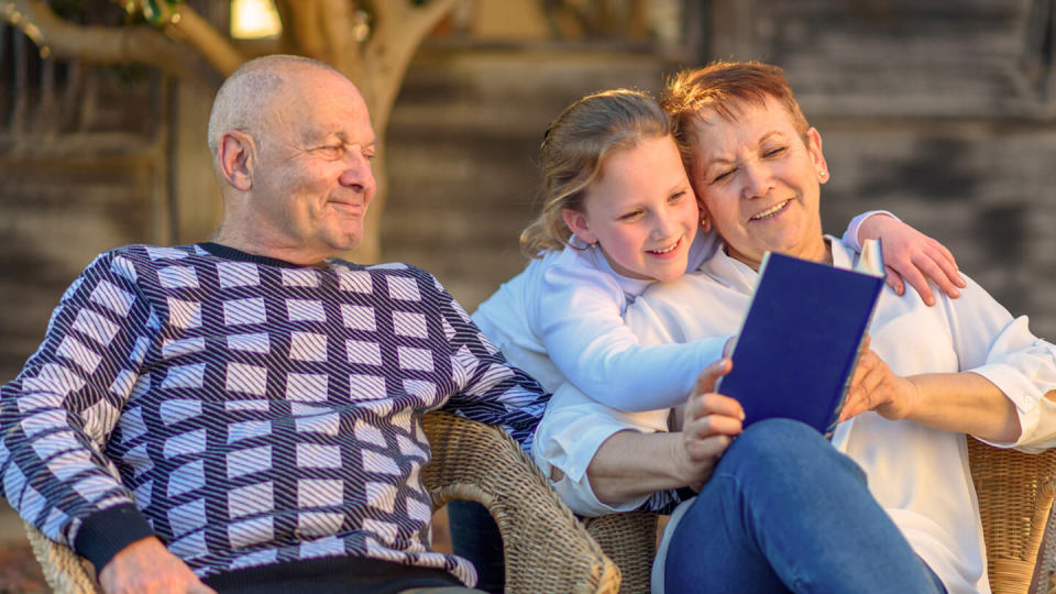 Senior couple reading a book with granddaughter in the sun