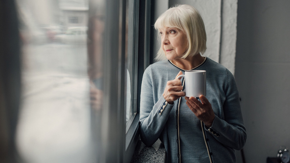 Mature woman with mug of coffee looking out of window