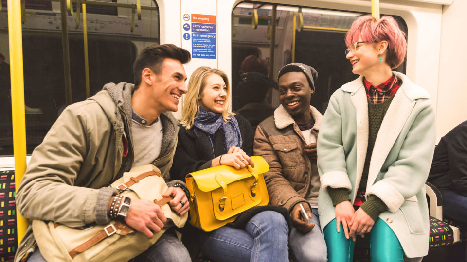 Group of teenagers on a train smiling and laughing