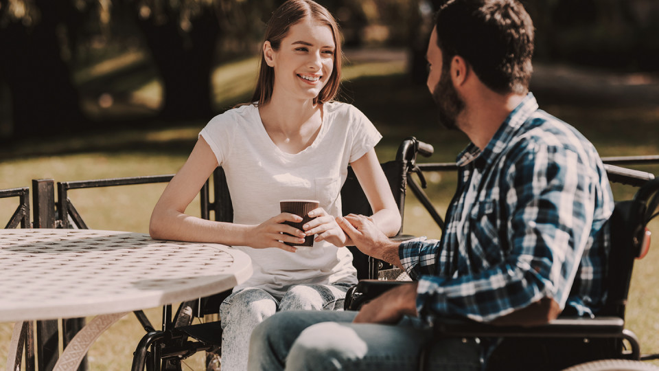Man in wheelchair with woman drinking coffee