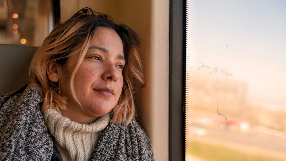 Smiling woman looking out of train window