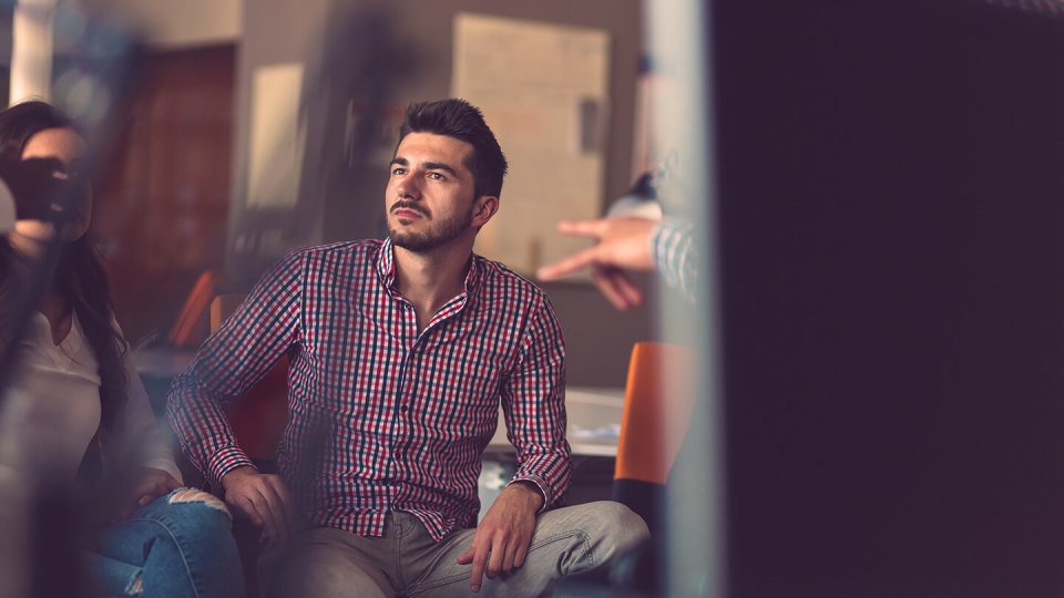 Man in checked shirt listening to colleagues