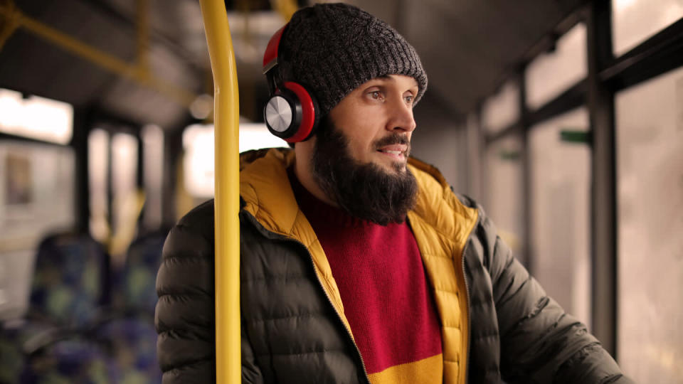 Mature man with headphones listening to music on public transport